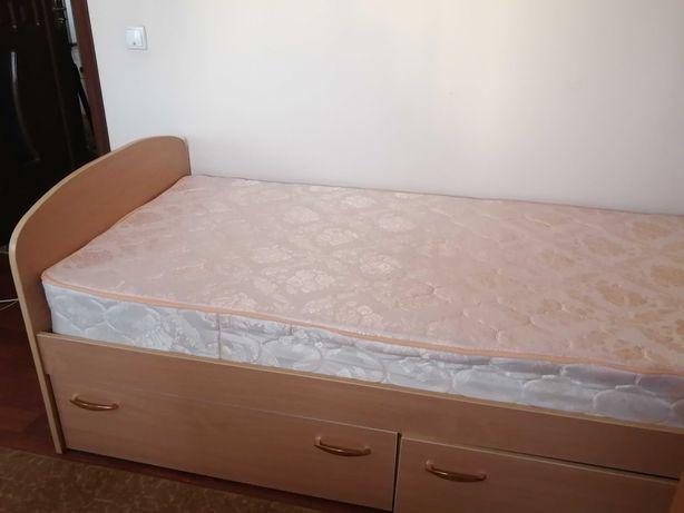 Кровать, сделанная под заказ из светлого дерева вместе с матрасом.