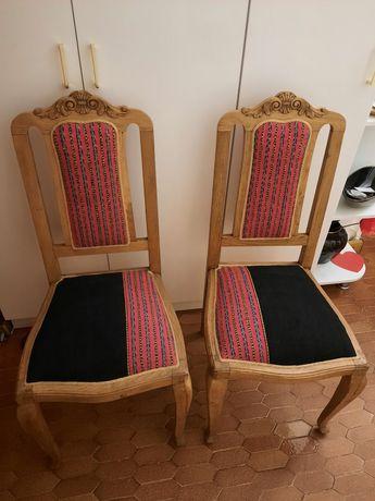 2 scaune din lemn tapițate cu țesătură populară.