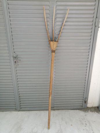 Много стари вили за сено и дървена закачалка.