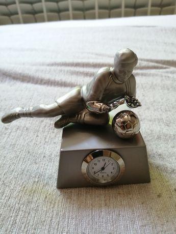 Метална статуетка на вратар с часовник.